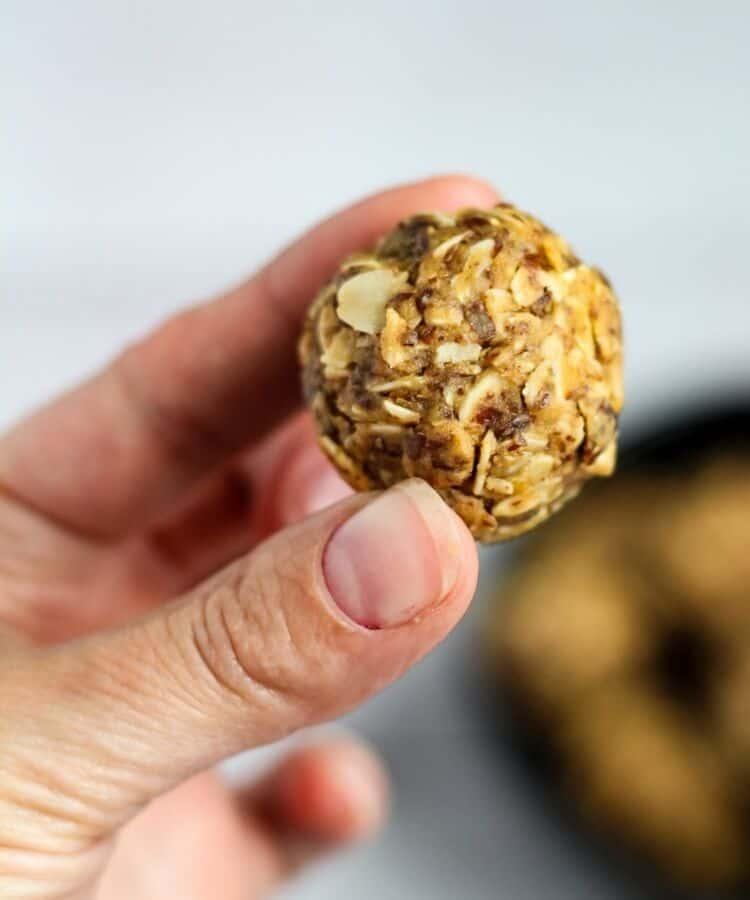 vegan protein energy ball held between fingers