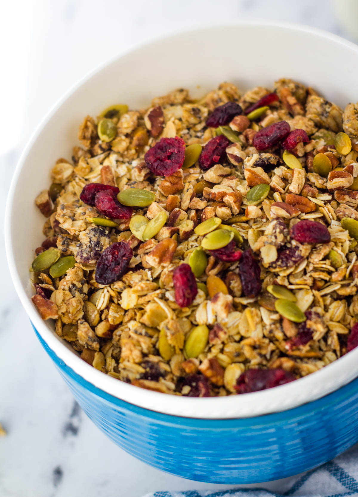 Granola with cranberries, and pumpkin seeds in blue and white stacked bowls.