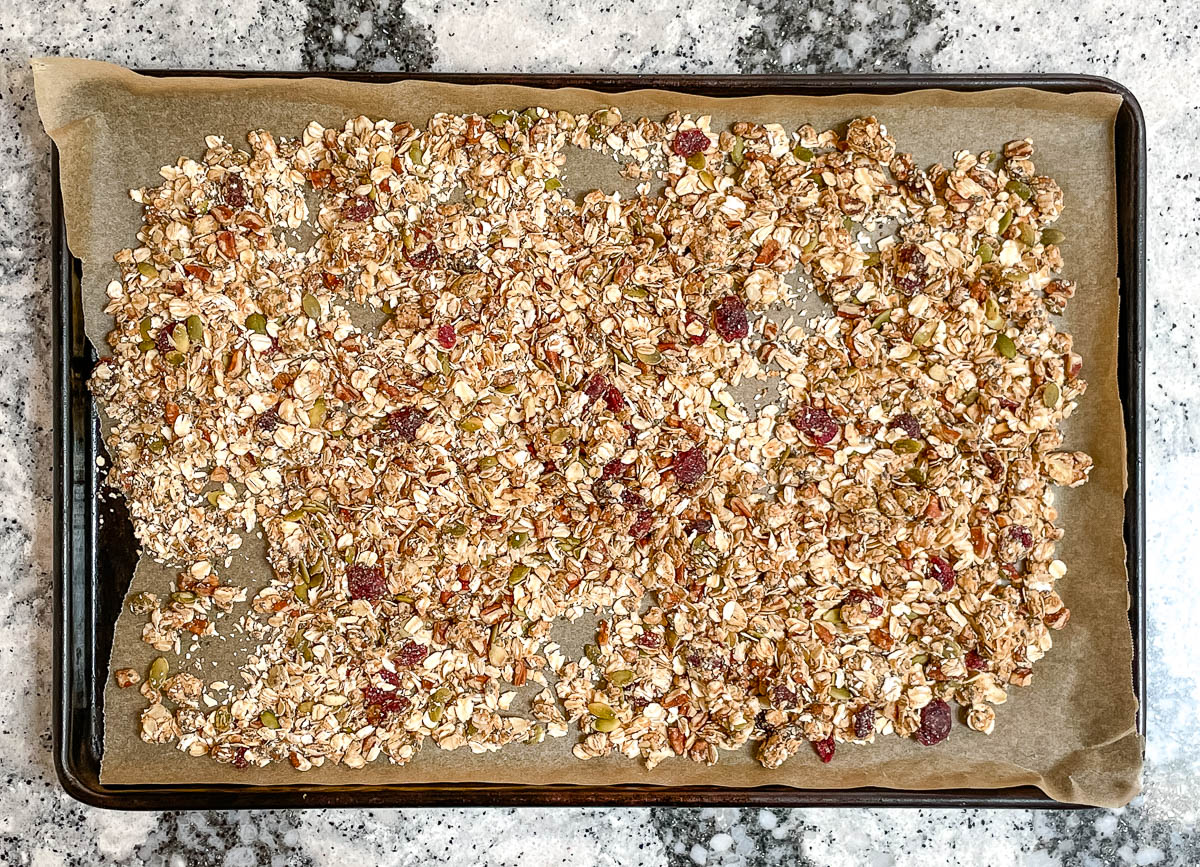 Granola spread out on baking sheet lined with parchment paper.