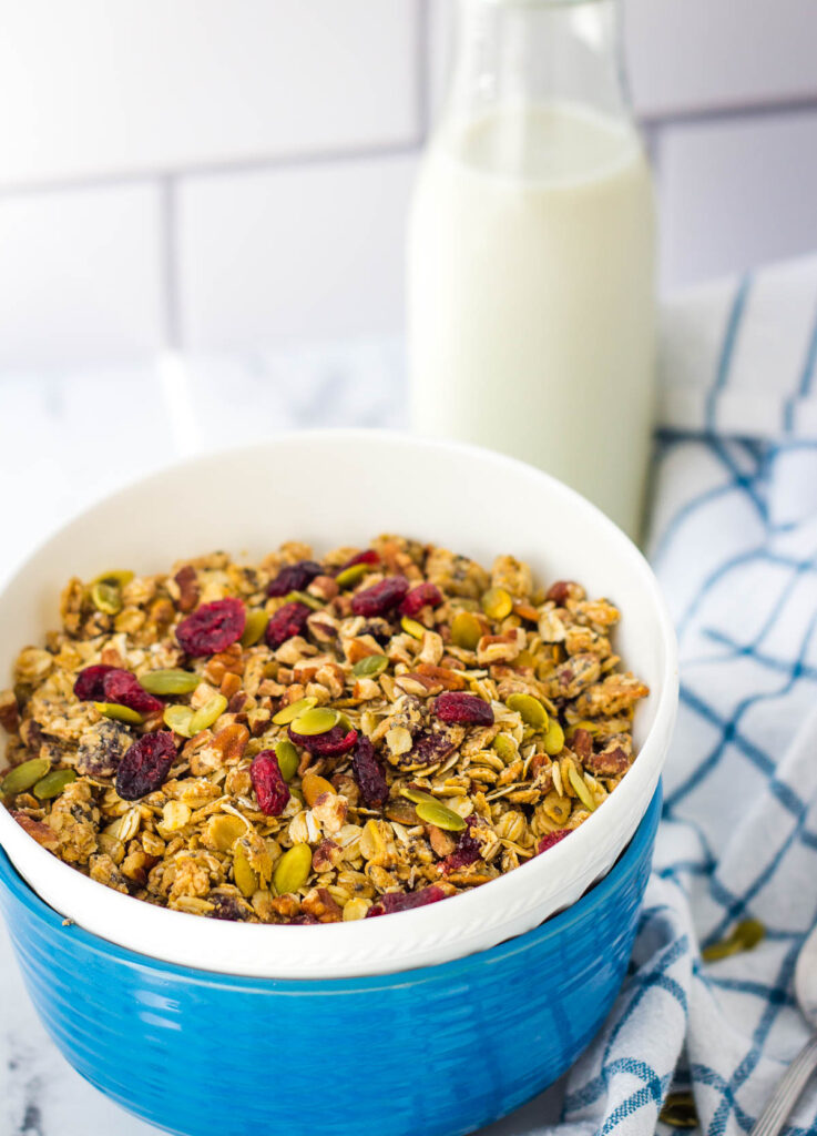 Granola in white bowl topped with dried cranberries and pumpkin seeds.