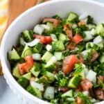 close up overhead of cucumber salad in white bowl