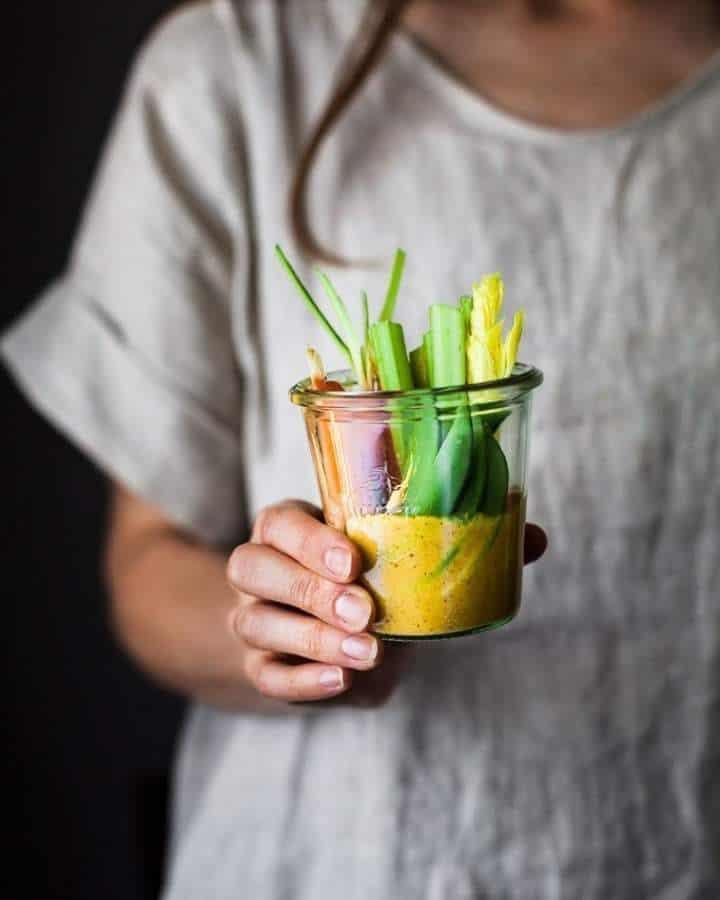 woman holding veggies in gold dip
