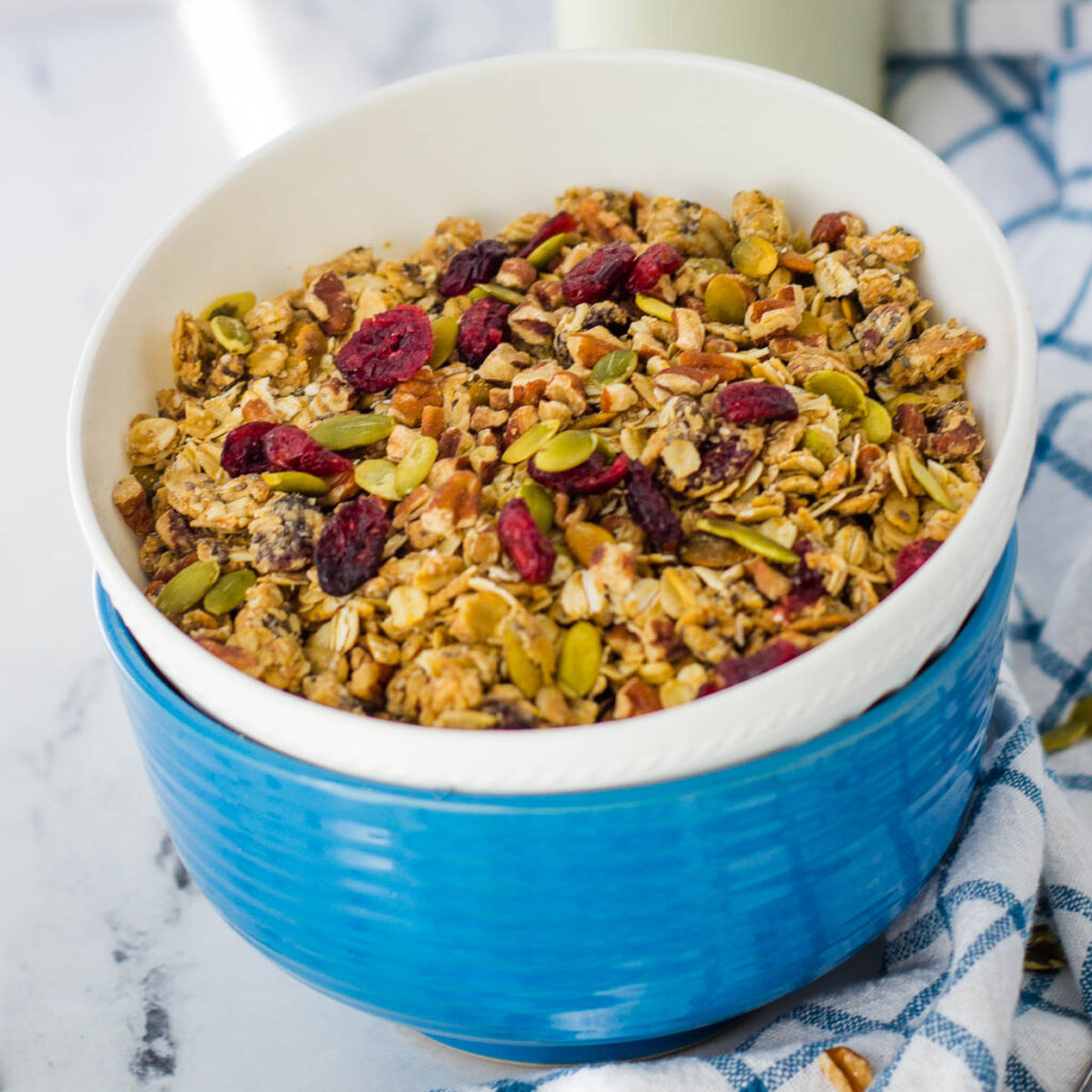 Sugar free granola with cranberries in blue and white bowls.