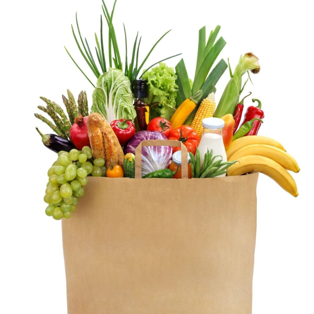 brown bag of groceries filled with items from a vegan grocery list like fresh fruits, and vegetables.