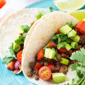 Whole wheat tacos filled with vegan taco meat, and topped with diced avocado, tomato, scallions, and cilantro.