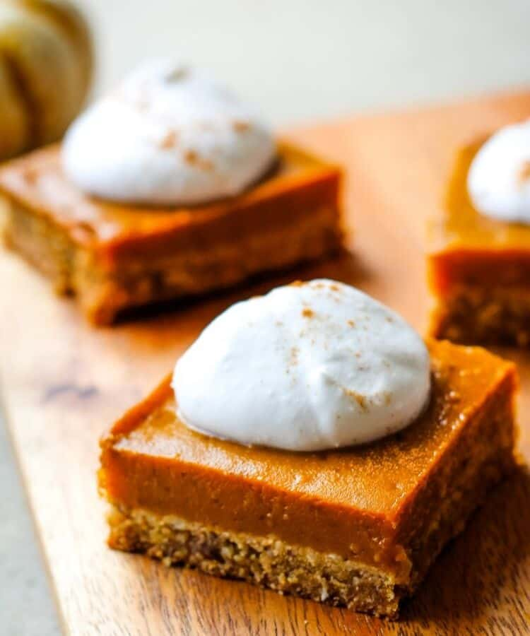 vegan gluten-free pumpkin pie bars topped with coconut whipped cream