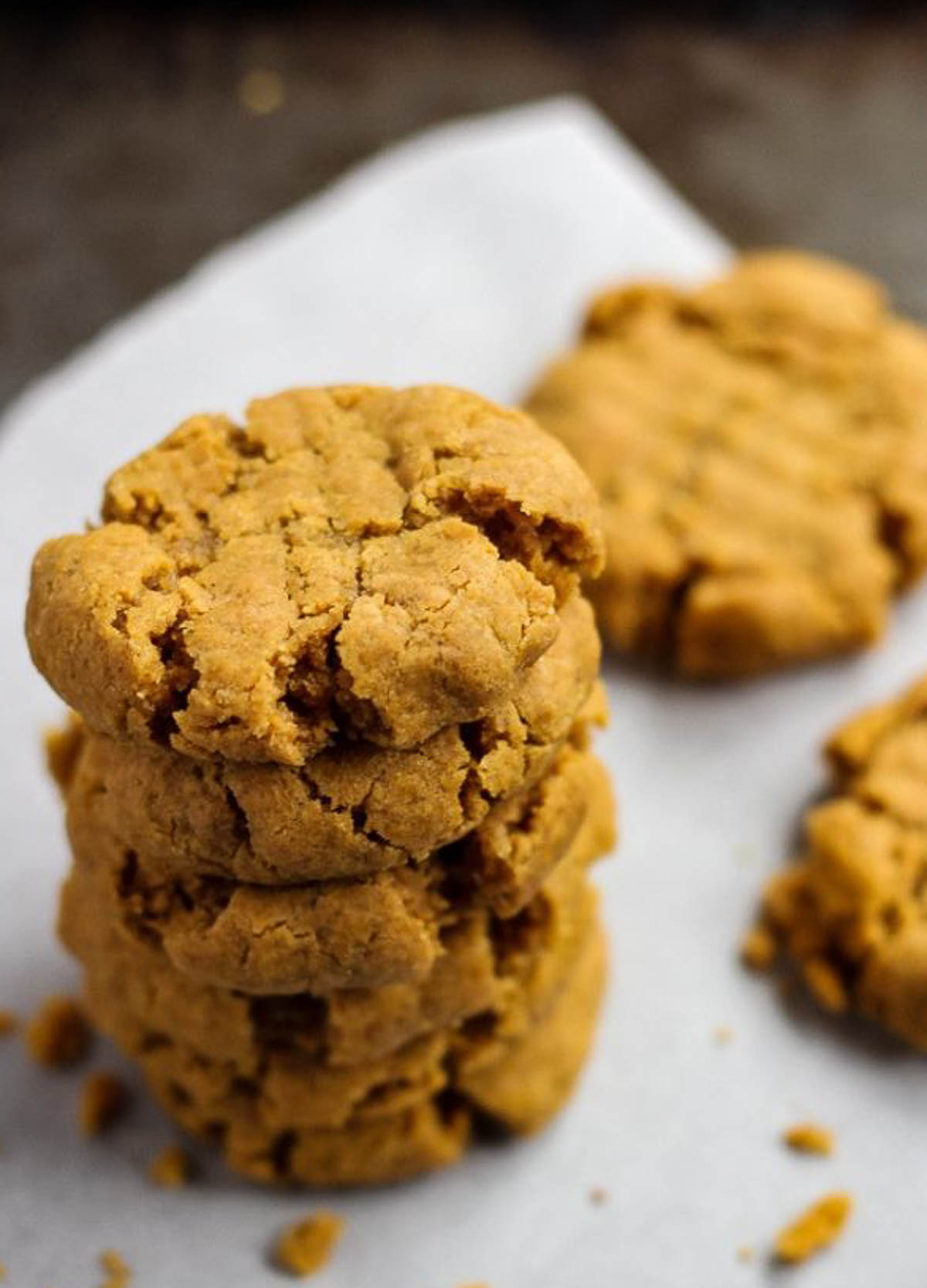 Stack of peanut butter cookies on white parchment paper.