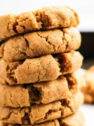Stack of almond flour peanut butter cookies on cookie sheet lined with parchment paper.