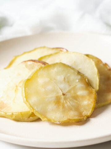 White plate of apple chips.