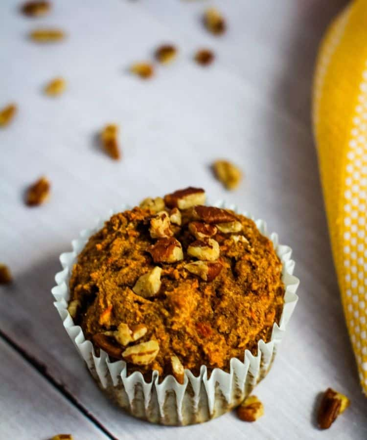 close up of a banana carrot muffin topped with nuts