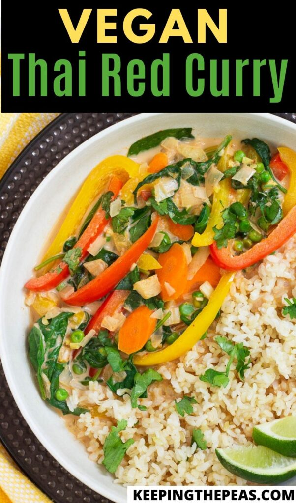 Vegan thai red curry with mixed vegetables and rice, served with wedges of lime.