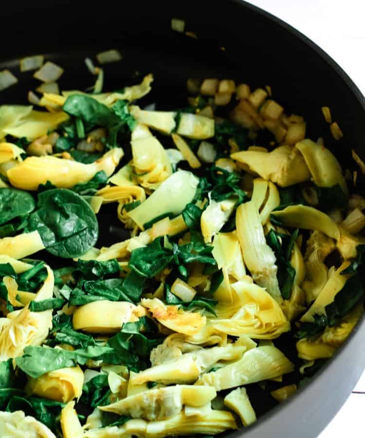 spinach and artichoke hearts in pan