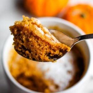 Spoon holding serving of pumpkin mug cake.