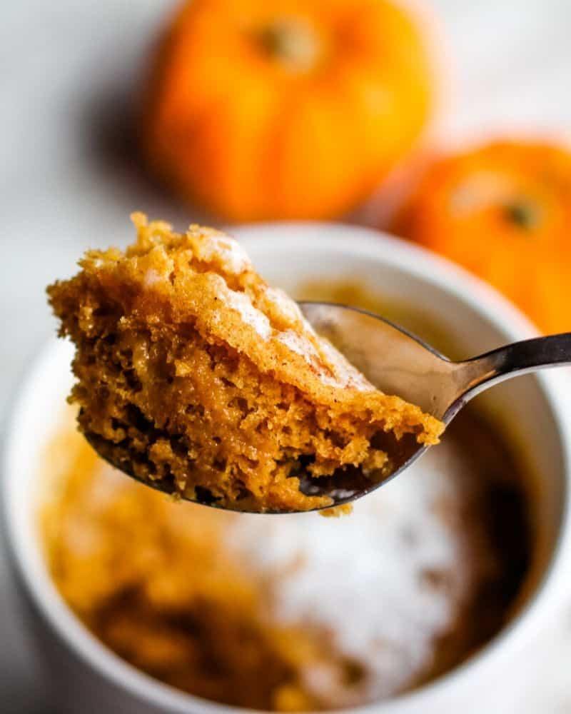 Spoon holding pumpkin mug cake.