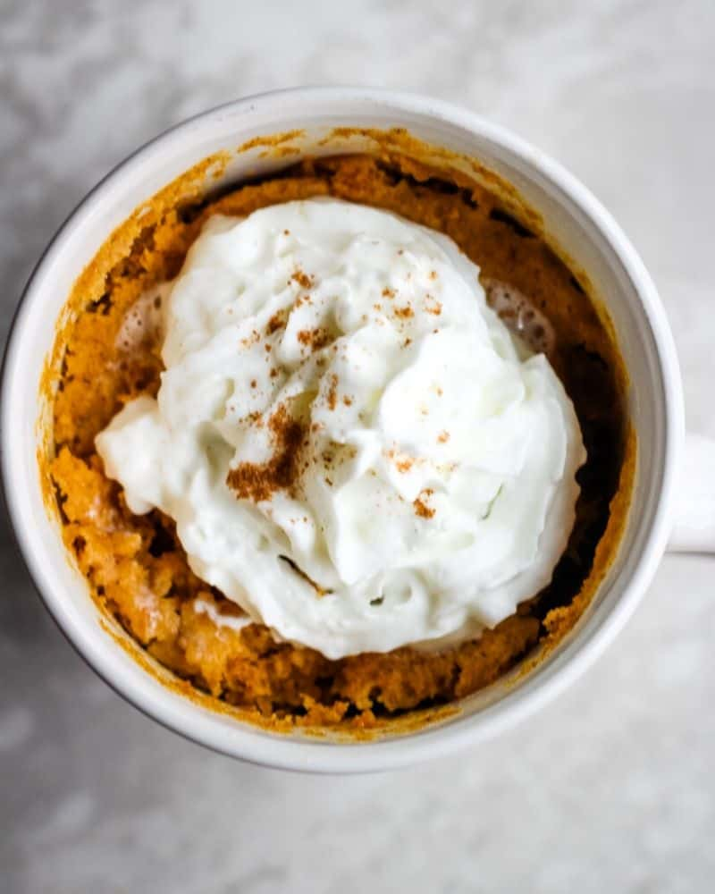 Overhead of pumpkin cake in mug topped with whipped cream and pumpkin pie spice.