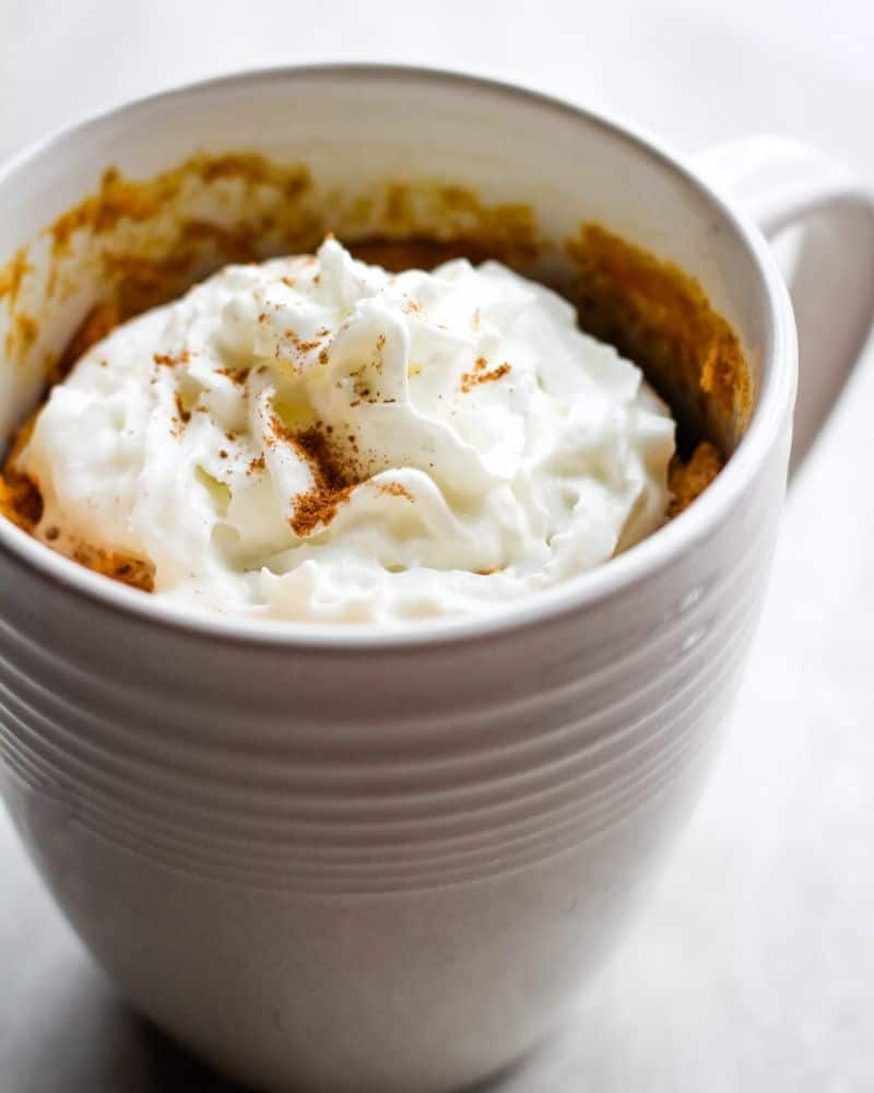 Pumpkin mug cake topped with whipped cream and pumpkin pie spice.