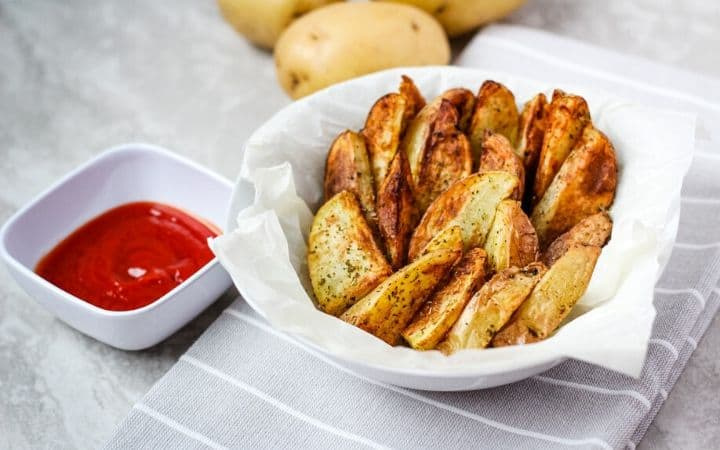 air fryer potato wedges in white bowl with side of ketchup