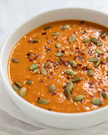 Bowl of butternut squash and red pepper soup topped with red pepper flakes and pumpkin seeds.