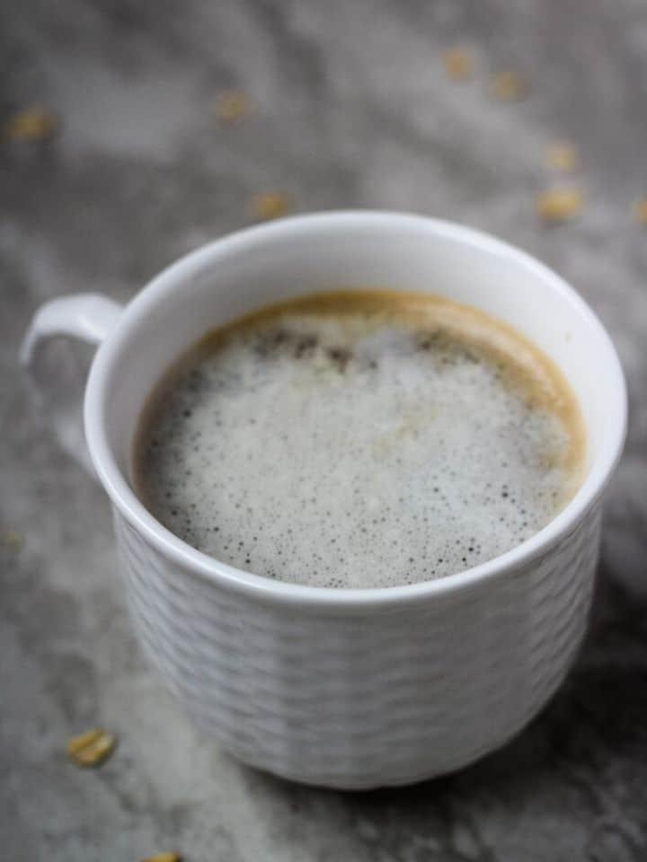 oat milk latte in white cup
