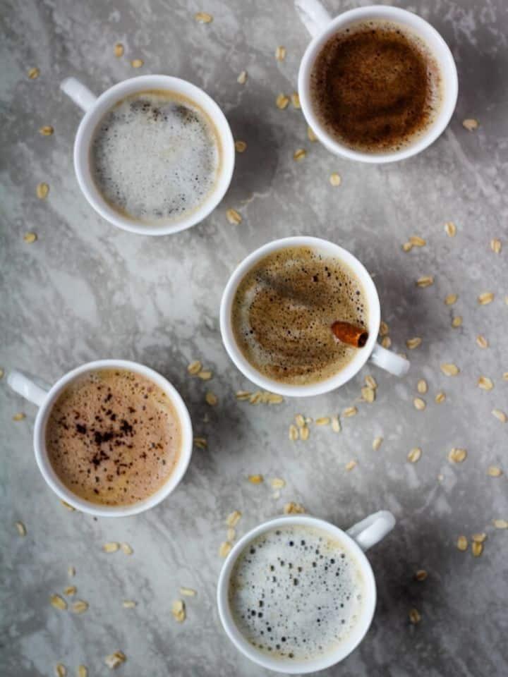 overhead 5 oat milk lattes on gray background