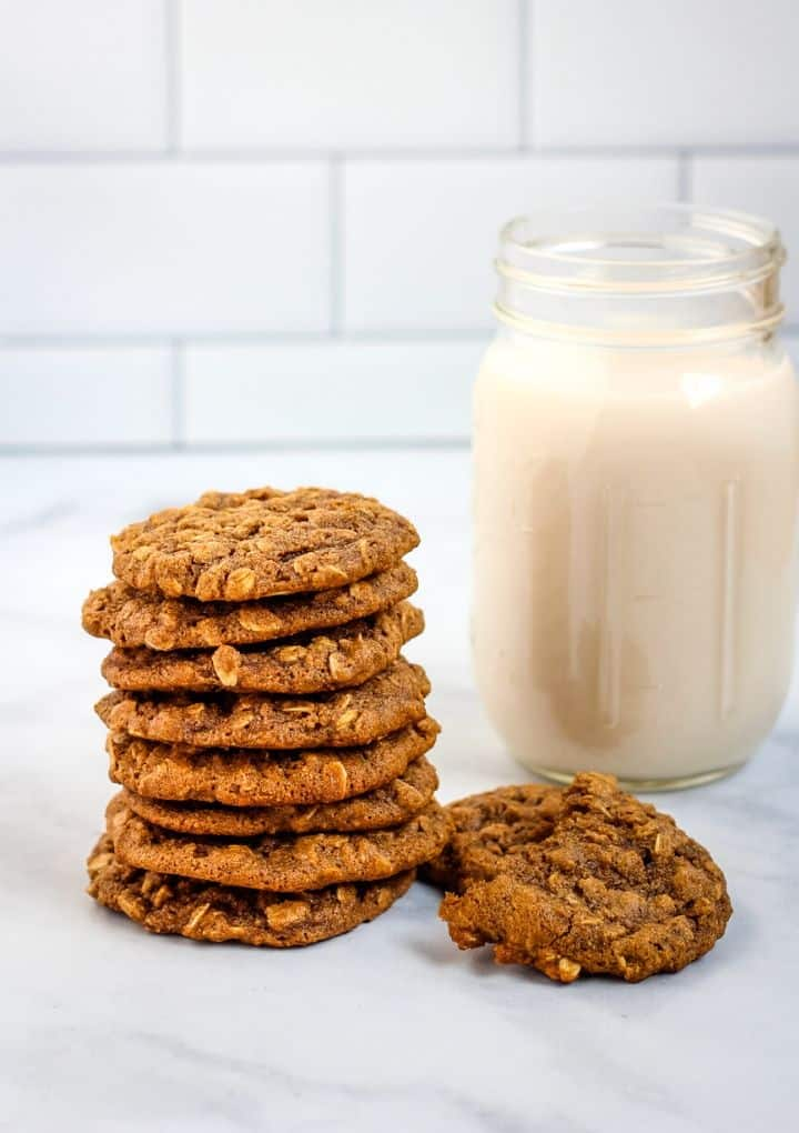 vegan oatmeal cookies in a stack with almond milk