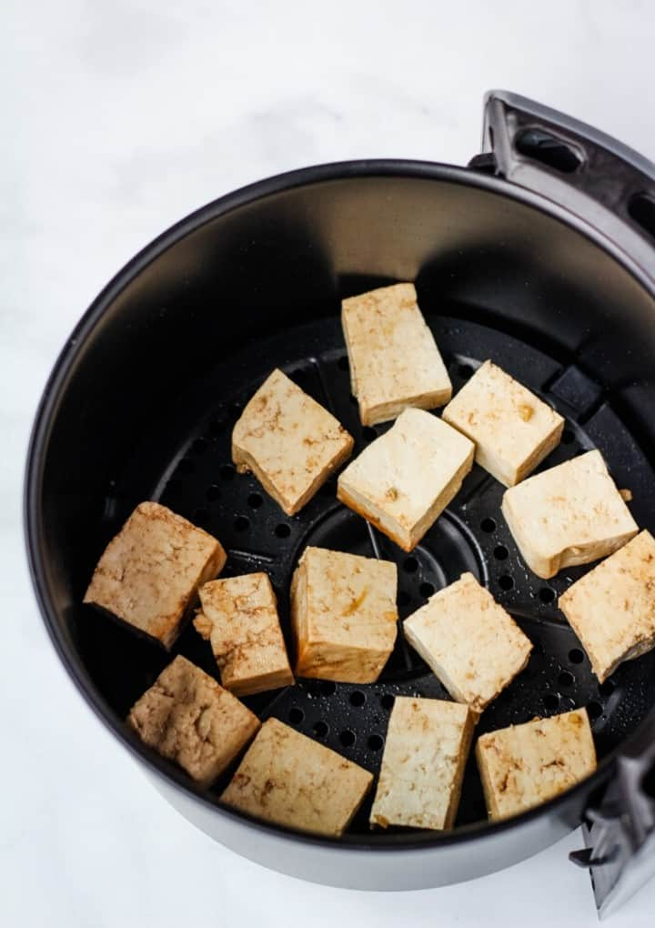 tofu in air fryer basket before it's cooked