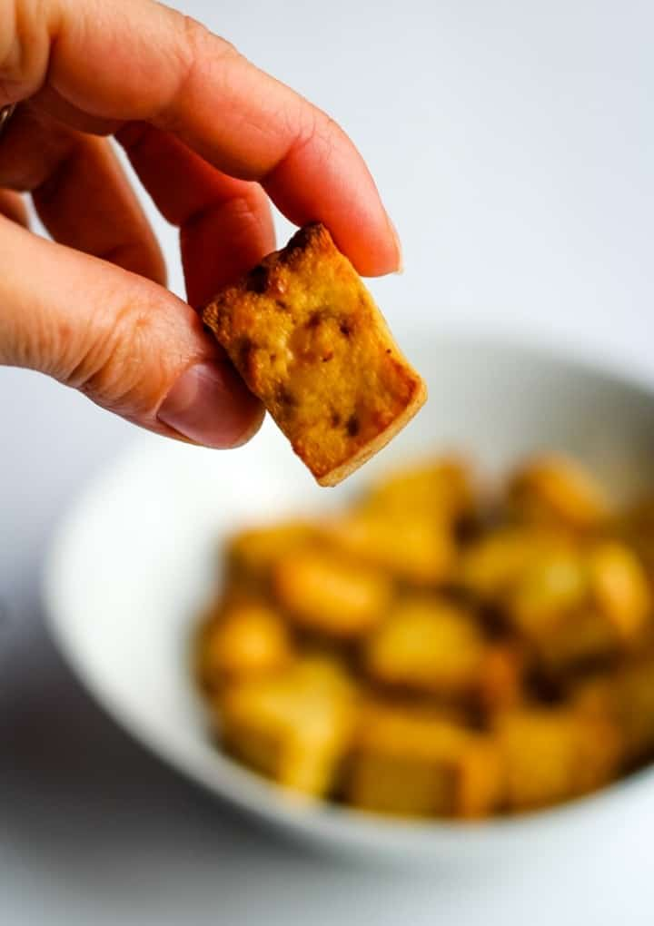 air fryer tofu bit in hand