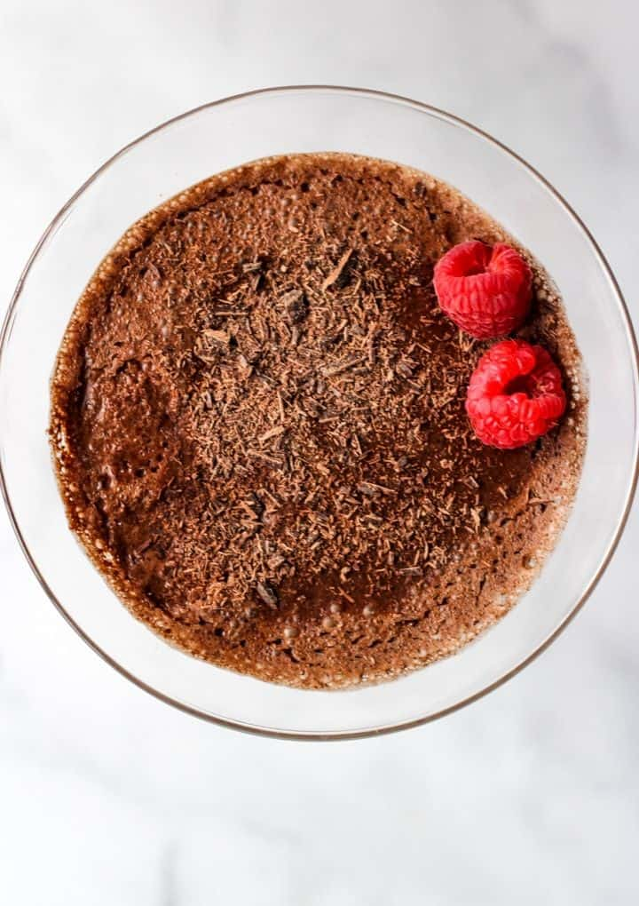 overhead of aquafaba chocolate mousse topped with two raspberries