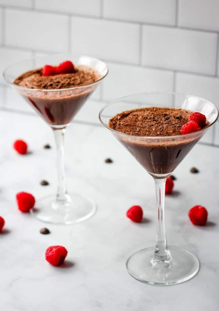 two aquafaba chocolate mousse desserts in martini glasses topped with two raspberries