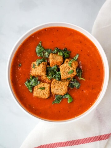 vegan tomato soup topped with croutons and basil