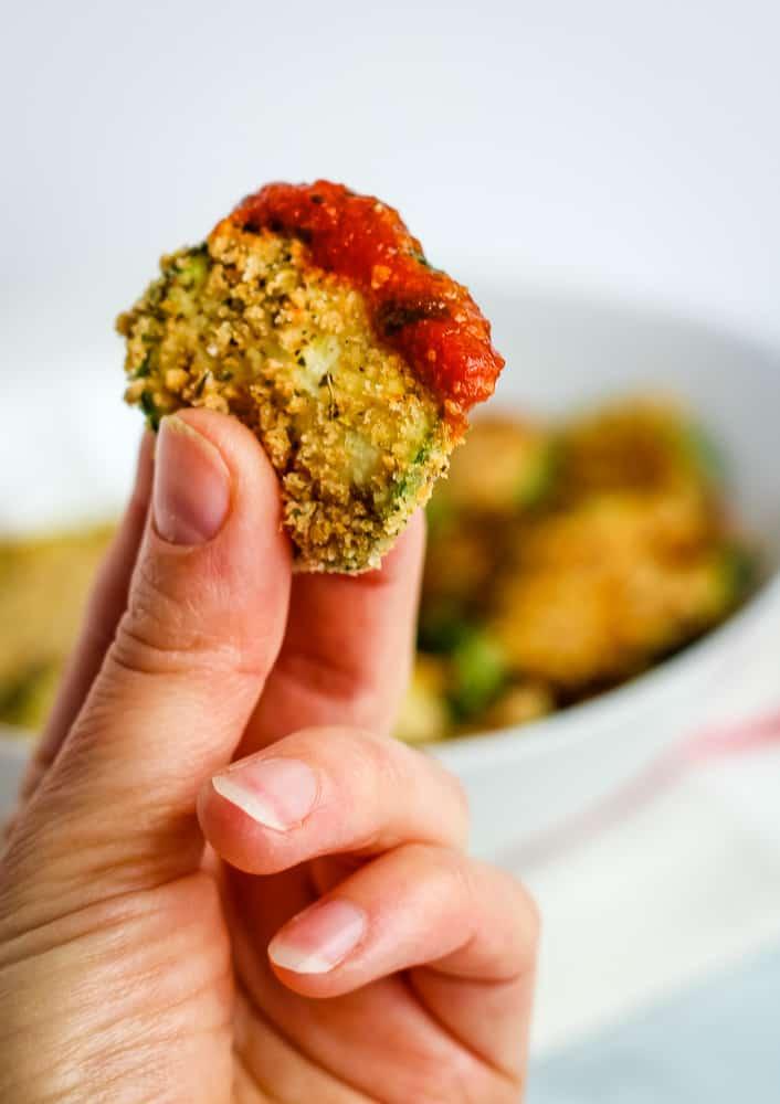 hand holding air fryer zucchini chip with marinara