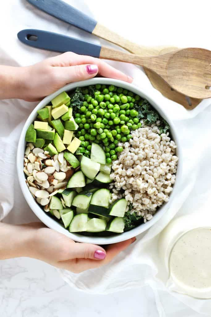 Green grain summer bowl with peas, avocado, cucumber, and almonds