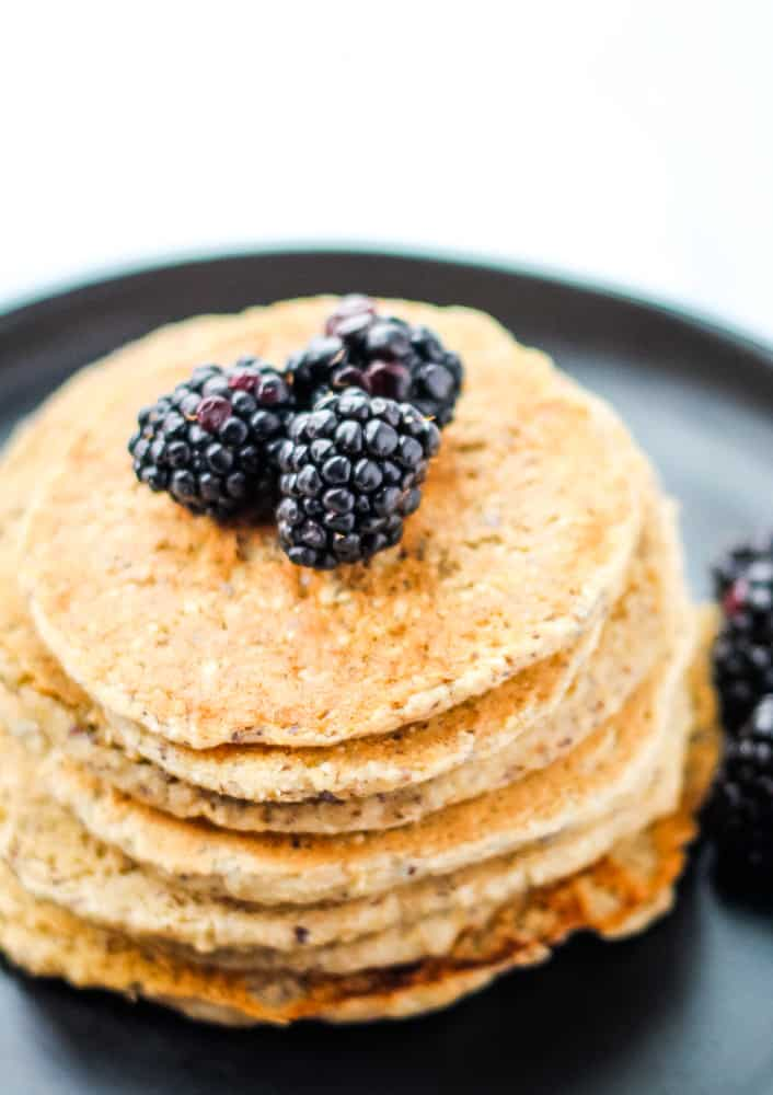 vegan protein pancakes topped with blackberries on black plate