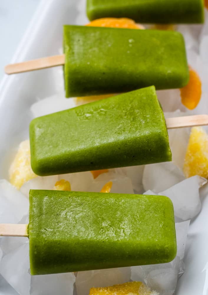 spinach mango popsicles on ice