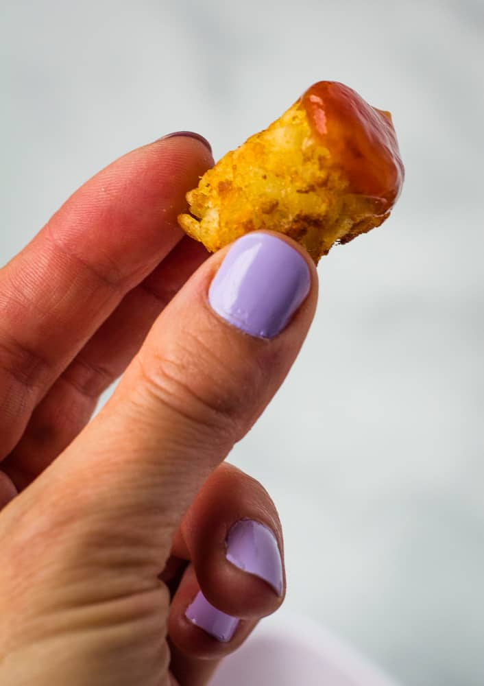 hand holding tater tot dipped in ketchup