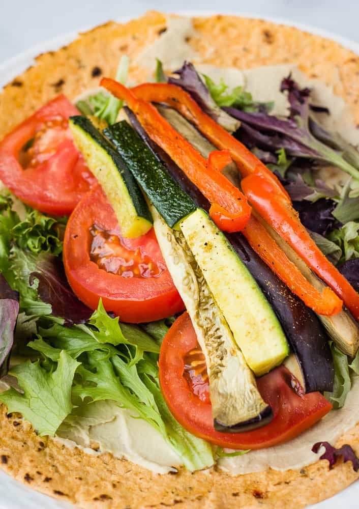 tortilla topped with roasted vegetables, tomato, and lettuce