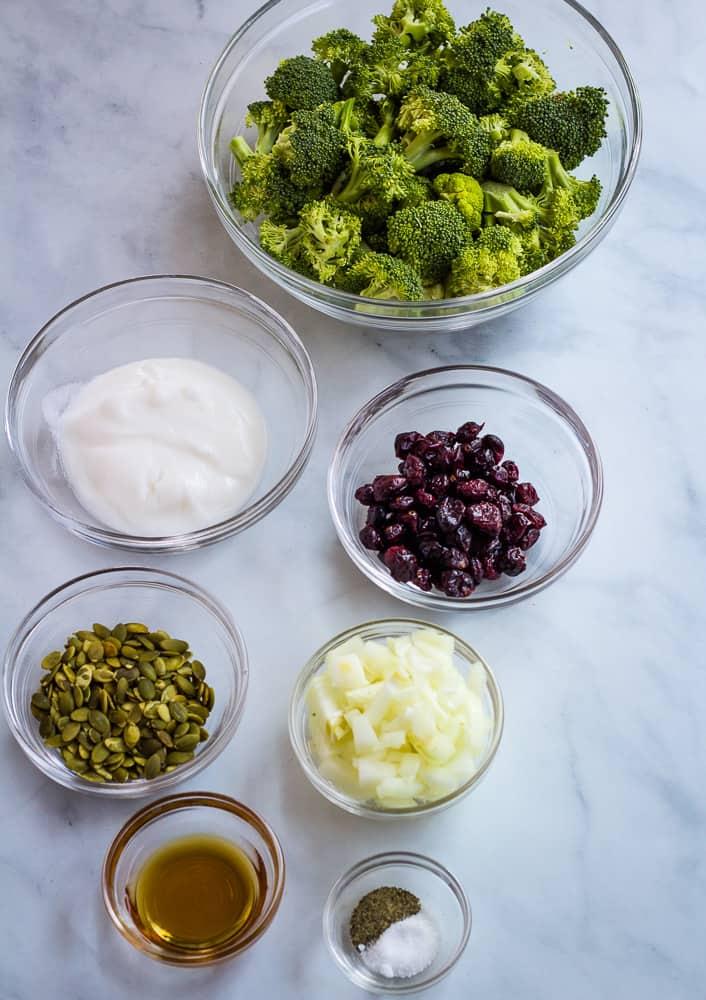 raw broccoli, onion, cranberries, yogurt, salt, pepper maple syrup in bowls