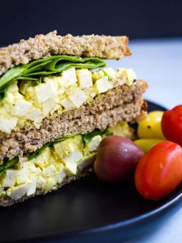 vegan egg salad sandwich with cherry tomatoes