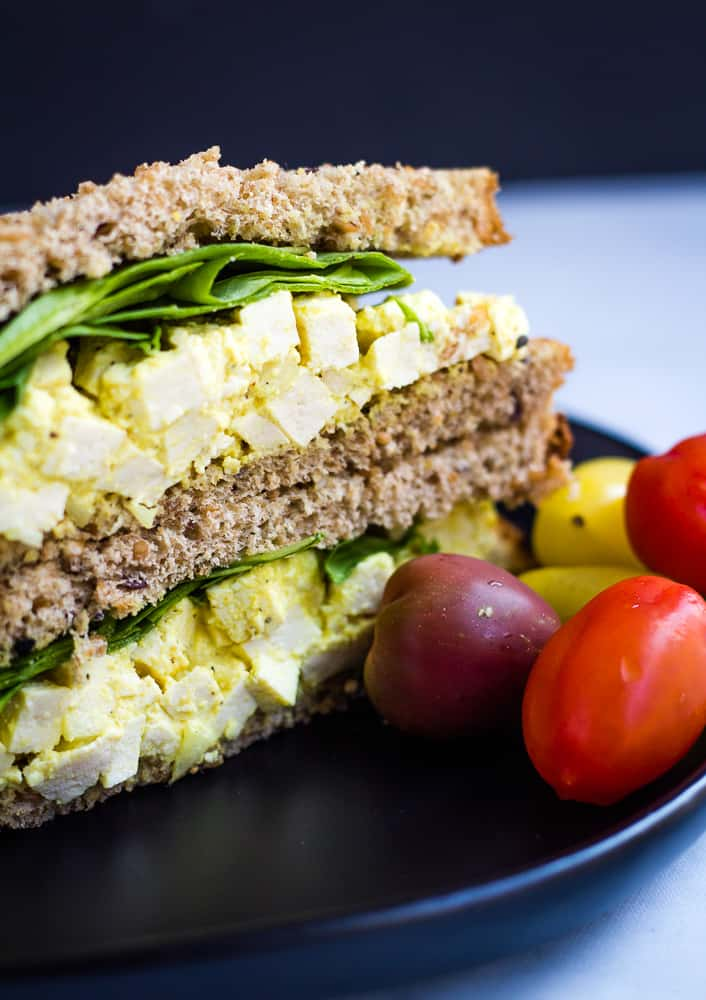 vegan egg salad sandwich with cherry tomatoes