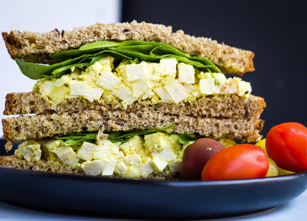 close up vegan egg salad sandwich with cherry tomatoes