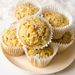 Several vegan zucchini muffins on peach plate.