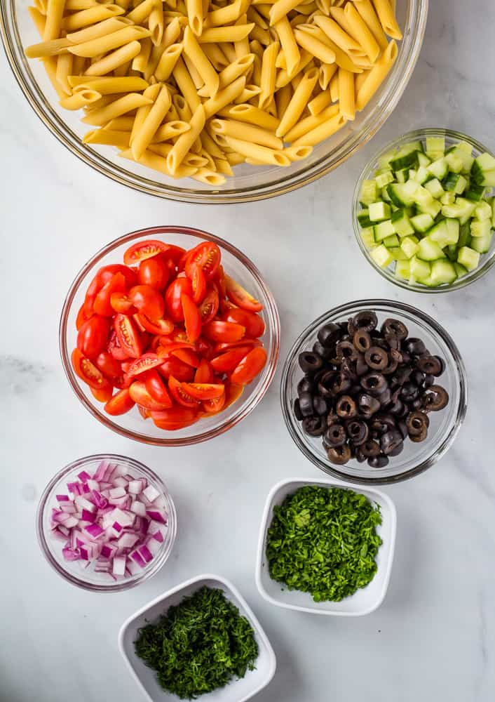 pasta, tomatoes, cucumbers, onion, olives, dill, and parsley