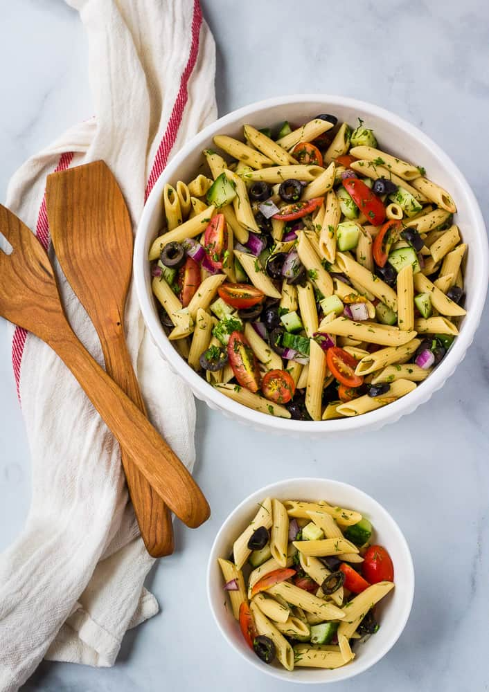 gluten free pasta salad in large white bowl and single serving bowl