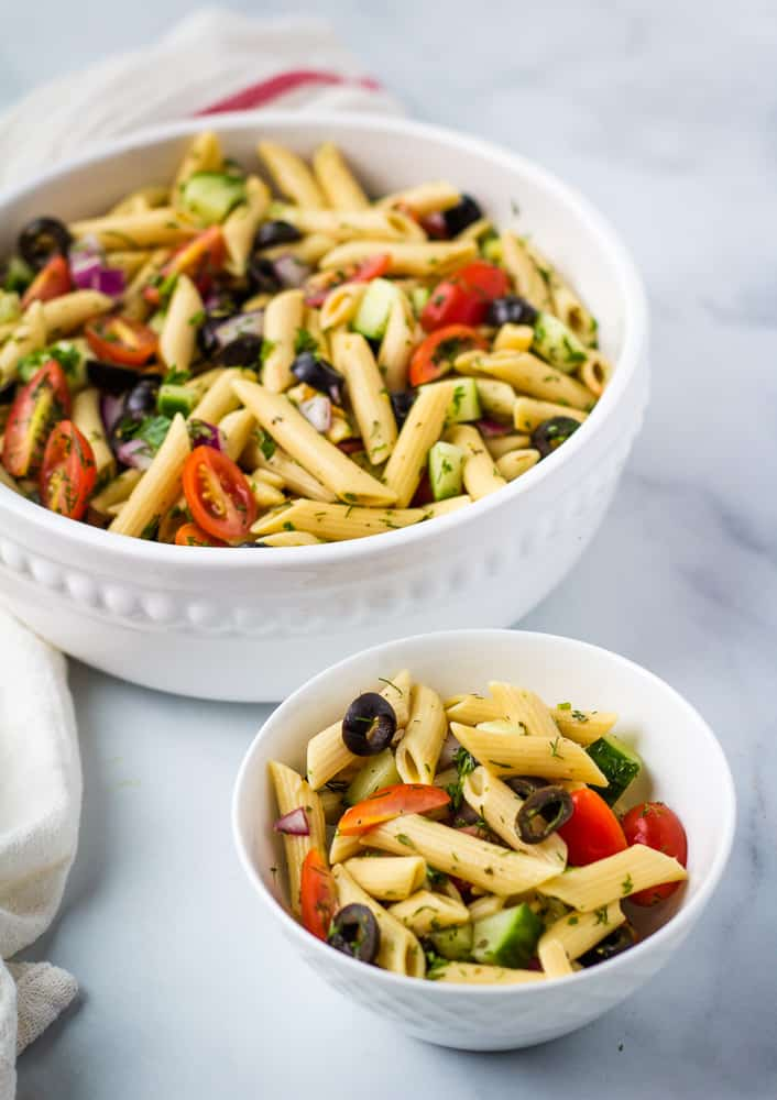 pasta salad in large white serving bowl and serving size in small bowl