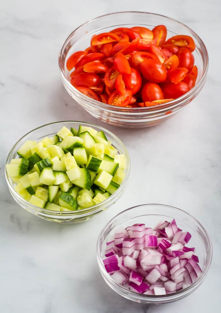 chopped tomatoes, cucumber, and red onion in glass bowls
