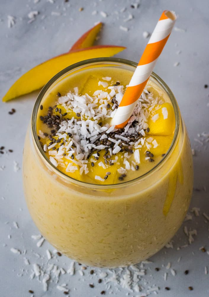 mango banana smoothie in glass with chia seed topping