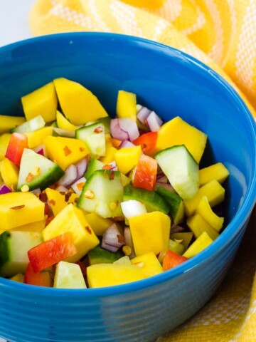 mango cucumber salad in blue bowl