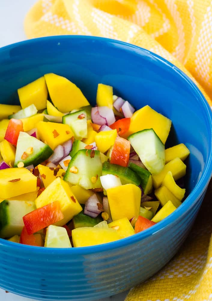 mango cucumber salad in blue bowl