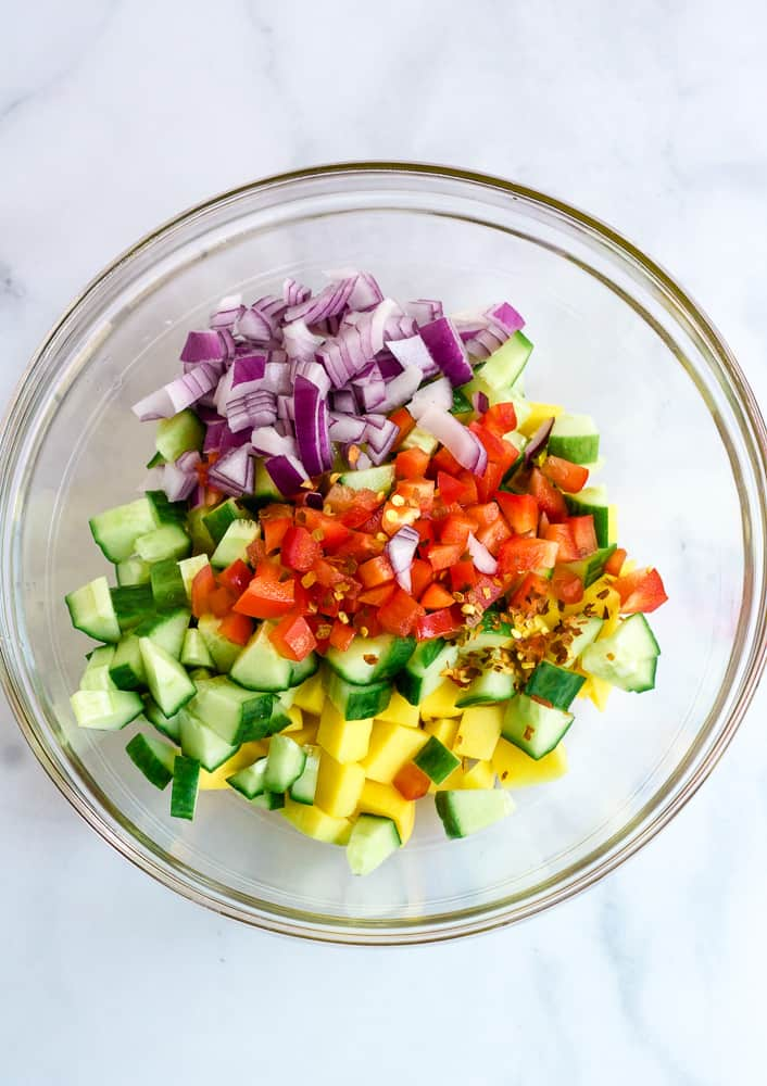 diced mangoes, cucumber, red onion, red pepper in glass bowl