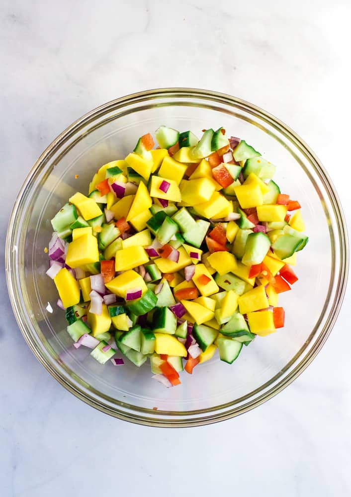 mango cucumber salad in glass bowl